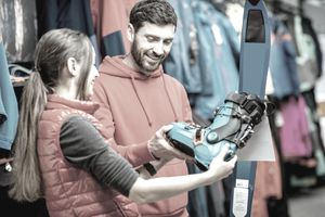 Man and woman choosing skiing equipment in the shop