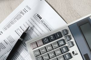 tax forms under a pen and calculator