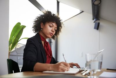 Confident young female financial advisor writing on diary