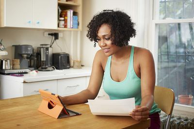 woman in blue tank top looking at ipad with paper in her hand