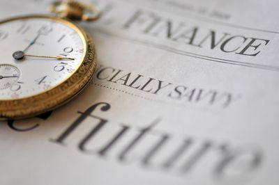 Old pocket watch on financial newspaper
