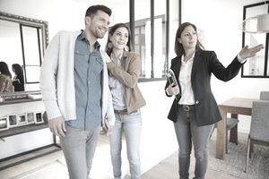Real estate agent showing a house to a young couple