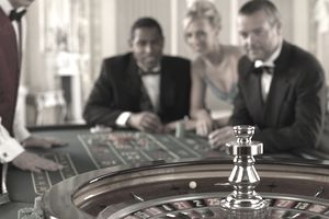 Adults in evening clothes gathered around a pinball table in a casino