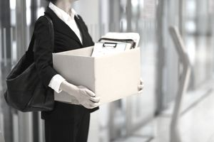 Torso of Woman Standing Holding Box of Office Papers as She Leaves an Office Building