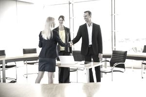 Couple shaking hands with real estate agent in office