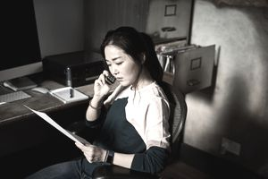 Portrait of Korean woman on cell phone reading important document