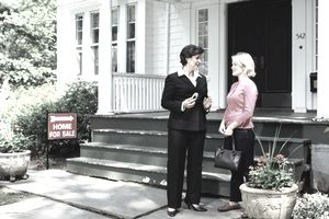 Female real estate agent and woman in front of house for sale