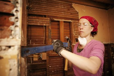 Woman stripping plaster walls in a home she is flipping