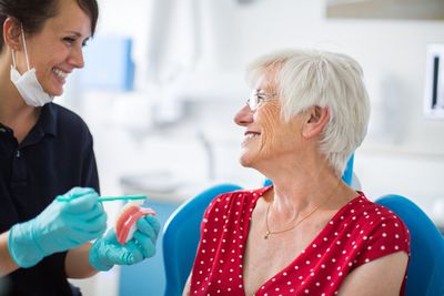 Dentist showing her patient how to brush teeth at clinic