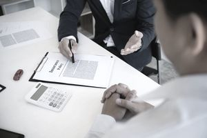 Torso and Hand of Insurance Agent Explaining an Insurance Policy Contract to a Customer Seated at Same Table