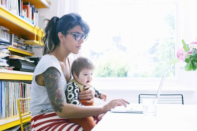 Woman with sleeve tattoo uses laptop with baby in lap