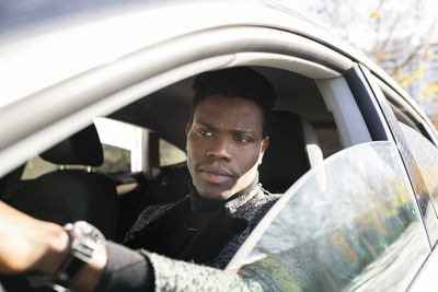 Serious young man drives car with window halfway down