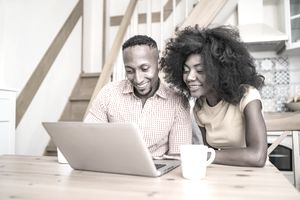 Couple checking their account on a laptop in the kitchen