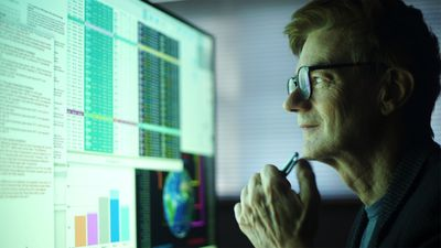 Man studying a large computer monitor displaying numerical data