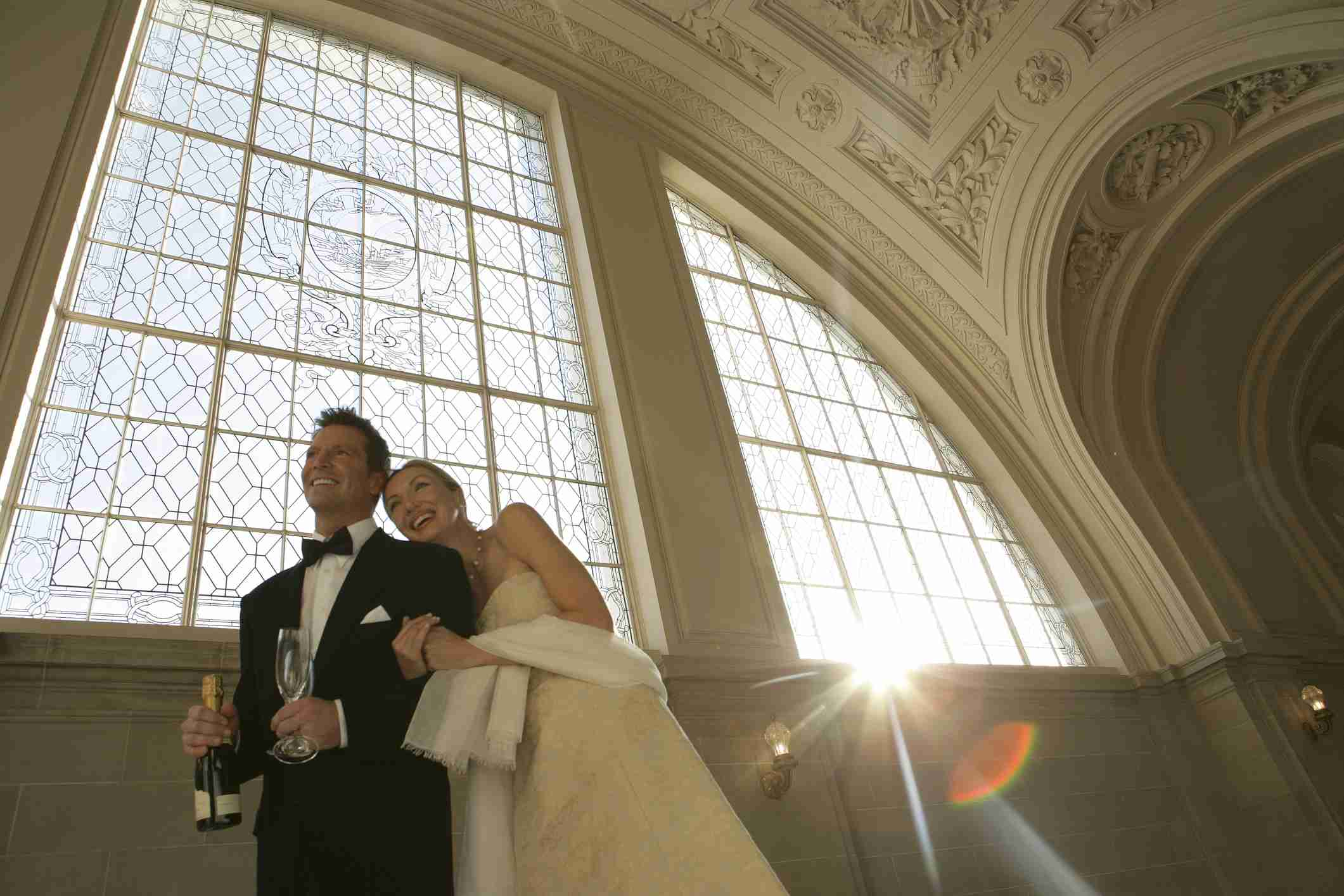 bride and groom walking through a cathedral-like entry area during their reception