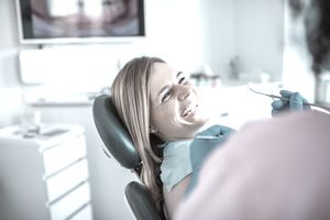 A woman sits in a dentist's chair, smiling.