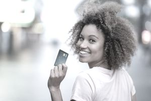A young woman looks over her shoulder while holding a credit card
