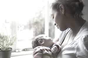 Mother holding a newborn baby beside a window