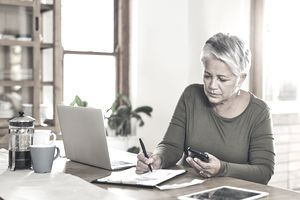 Shot of a mature woman going through paperwork at home