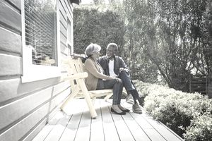 Senior retired couple sitting on front porch