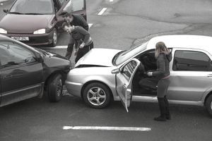Two men looking at car collision on road; woman standing near car