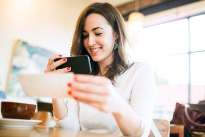 Woman taking photo image on phone of a remote deposit while seated in a cafe