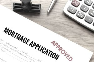 an approved mortgage application near a calculator on a table