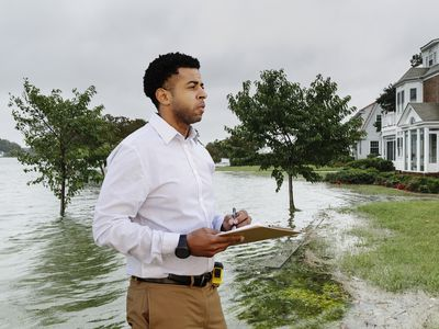 An insurance adjuster with a clipboard surveys flood damage to several houses