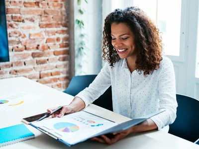 A woman views the annual report for company she is interested in.