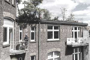 Woman Standing on Balcony of Brick House