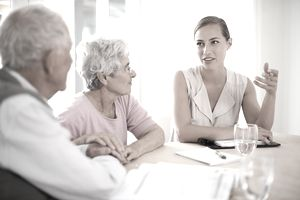 An older couple discussing life insurance with a younger insurance agent.