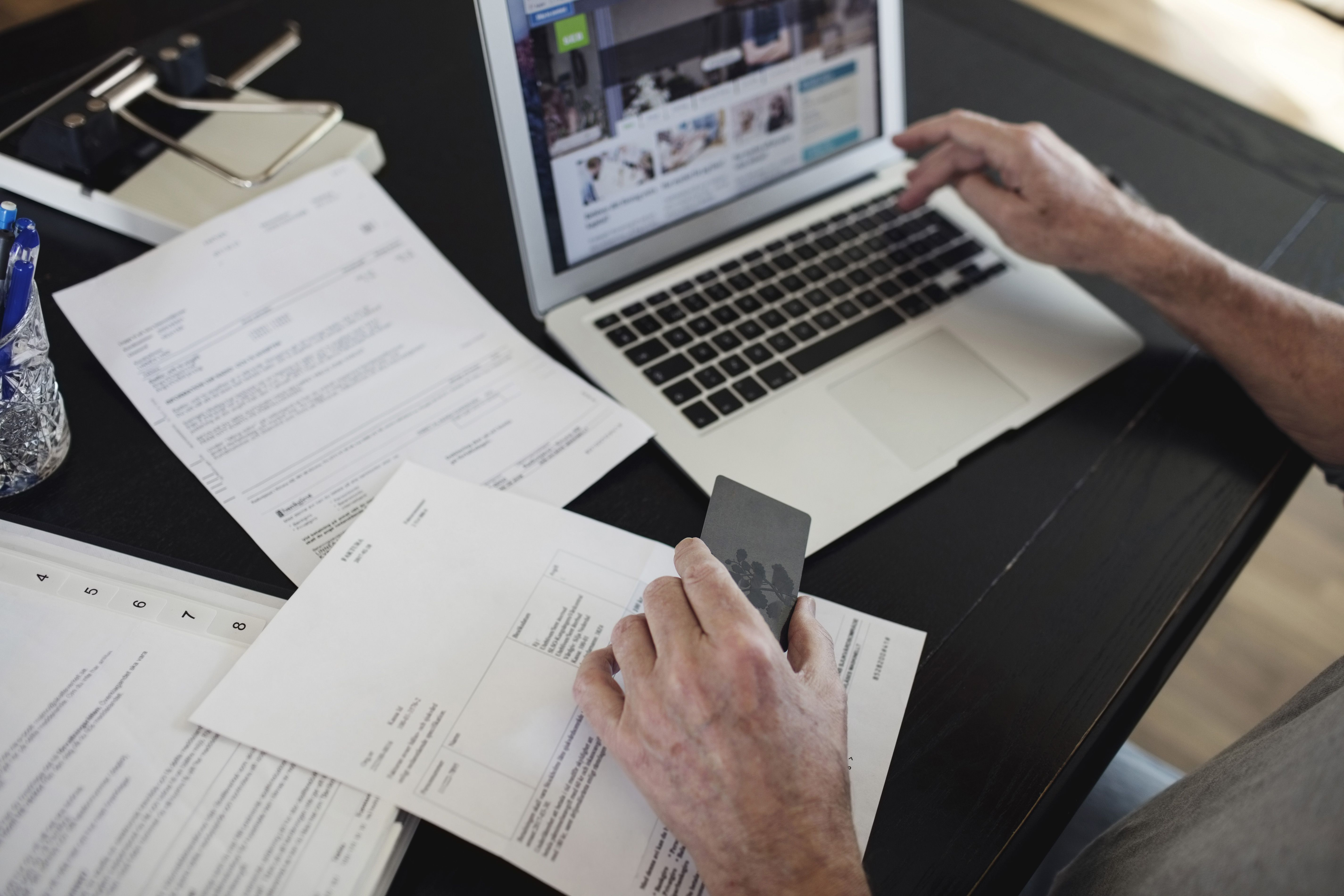 Close-up of a man's hands doing paperwork and paying bills on a laptop