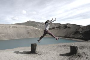Woman Jumping Against Lake And Volcano Crater