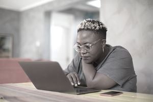 Black woman looking closely at laptop