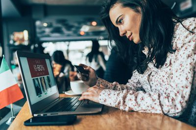 Woman shopping online on a laptop in a cafe