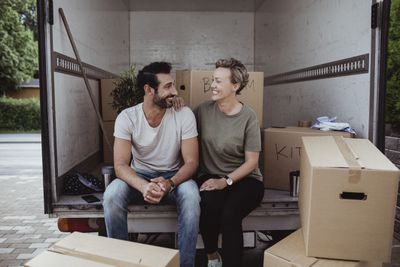 Smiling male and female partners looking at each other while sitting by cardboard boxes in van