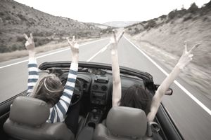 Driver and passenger with hands up in a convertible, driving down a desert highway