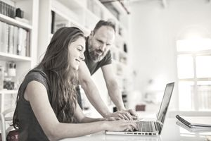 Father watches daughter working on a laptop at home.