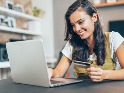 Woman smiling while holding a credit card and paying her bill online.