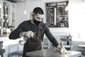 Young man barista with face mask and gloves standing in coffee shop, disinfecting tables.