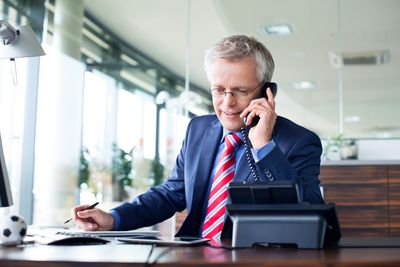 Investment advisor on phone discussing corporate bonds with a client