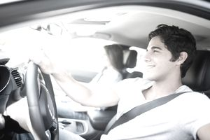 A young man smiles as he drives his car and his girlfriend sits in the passenger seat
