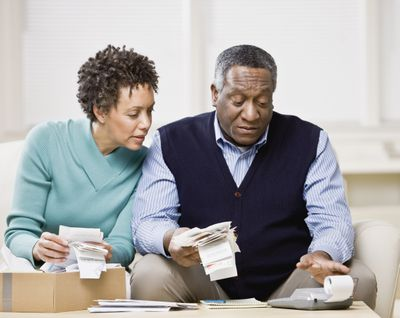 Middle-aged couple adding up receipts