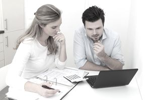Man and woman sitting at table with file, calculator and laptop