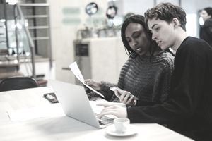 young man and woman looking at papers and laptop screen in cafe