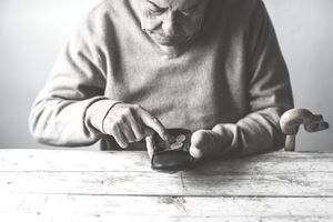An elderly man looks for some money from his wallet