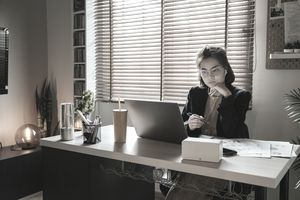 young person in black blazer sitting at desk with computer in front of her in dimly lit room