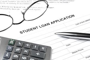 student loan application with glasses, calculator, and pen