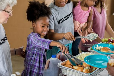 Little girl volunteers with her family at a soup kitchen