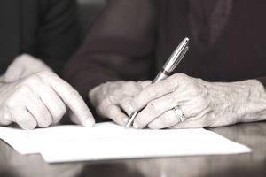 A senior citizen signing a document.